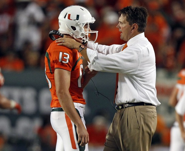University of Miami head coach Al Golden talks with punter Dalton Botts during first quarter in Miami